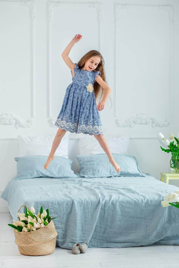 Retrato de una muchacha de ojos azules hermosa, niña entre las flores de la primavera en un cuarto brillante imágenes de archivo libres de regalías