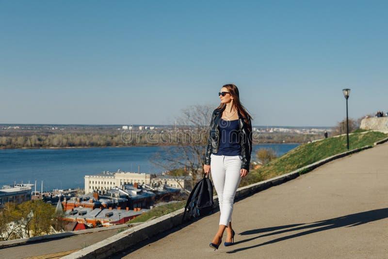 Retrato de una muchacha oscuro-cabelluda elegante en gafas de sol, ella est? en una chaqueta de cuero imágenes de archivo libres de regalías