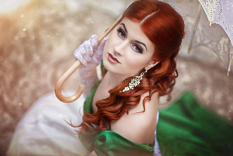 Retrato de una muchacha pelirroja joven hermosa en un vestido verde medieval con un paraguas Photosession de la fantasía fotos de archivo libres de regalías