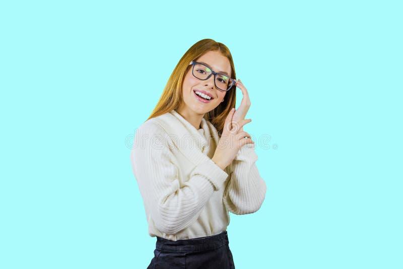 Retrato de una muchacha pelirroja linda en vidrios y de un suéter blanco que sostiene los vidrios con una mano y que pone su otra foto de archivo