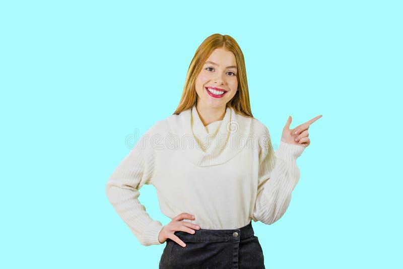 Retrato de una muchacha pelirroja linda que está mirando la cámara que sonríe, celebrando una mano en su correa, y mostrar imagen de archivo