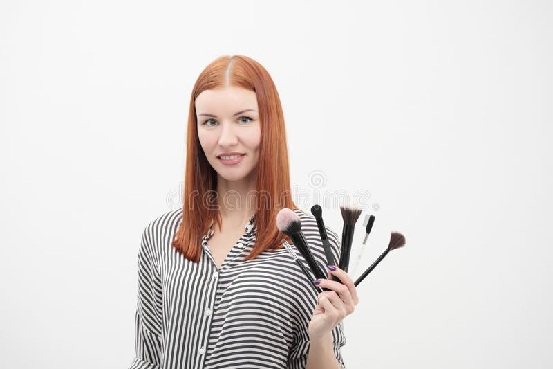 Retrato de una muchacha pelirroja, maquillaje del actor, profesional en el fondo blanco Brochas y paleta a disposición fotos de archivo