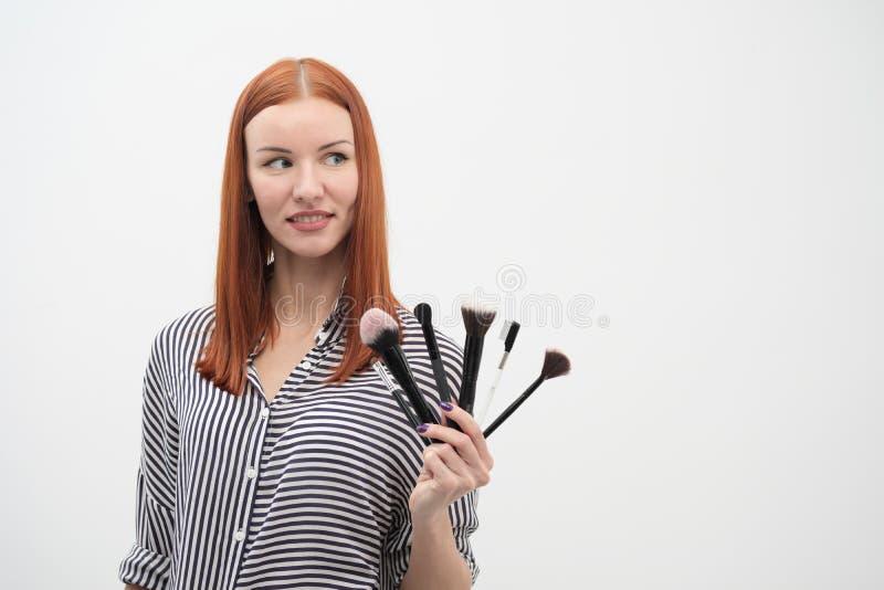 Retrato de una muchacha pelirroja, maquillaje del actor, profesional en el fondo blanco Brochas y paleta a disposición foto de archivo