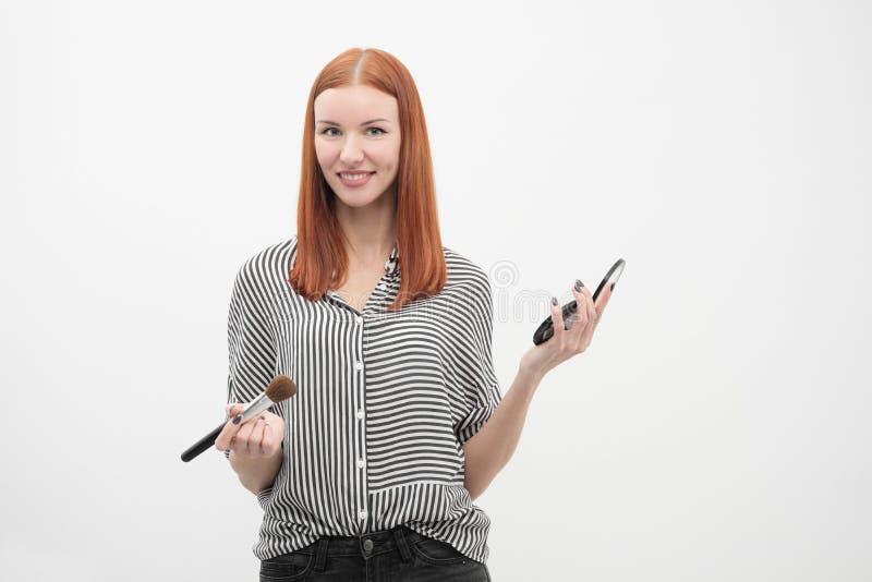 Retrato de una muchacha pelirroja, maquillaje del actor, profesional en el fondo blanco Brochas y paleta a disposición imagen de archivo