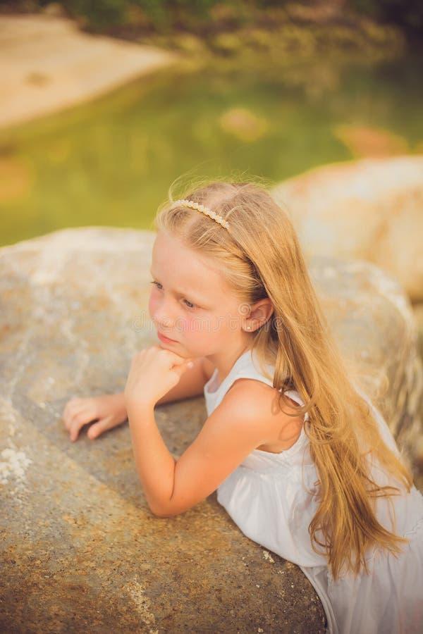 Retrato de una muchacha pensativa en un vestido blanco con el pelo largo con un borde en la playa al día de verano imagenes de archivo