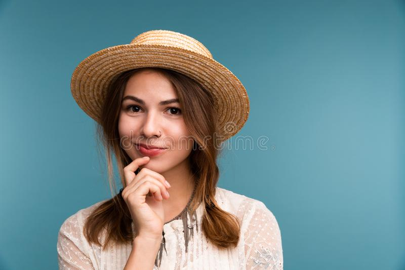 Retrato de una muchacha pensativa joven en el sombrero del verano aislado sobre fondo azul fotografía de archivo libre de regalías