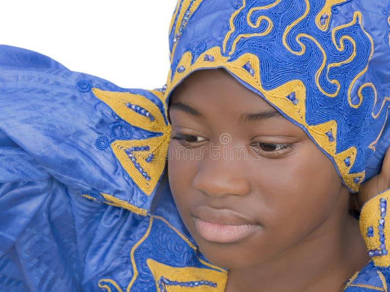 Retrato de una muchacha preciosa que ajusta un pañuelo azul, aislado foto de archivo libre de regalías