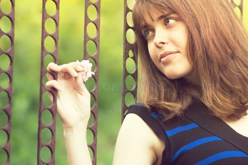 Retrato de una muchacha que lleva a cabo las manos en la puerta fotos de archivo libres de regalías