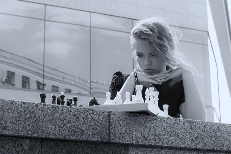 Retrato de una muchacha que mira el tablero de ajedrez fotos de archivo