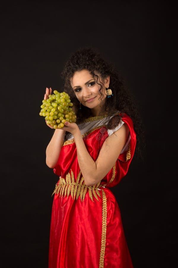 Retrato de una muchacha rizada que sostiene un manojo de uvas fotos de archivo libres de regalías