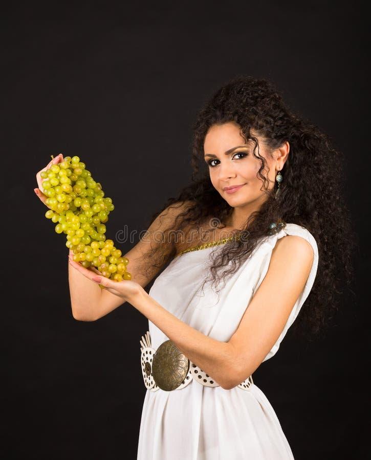 Retrato de una muchacha rizada que sostiene un manojo de uvas foto de archivo