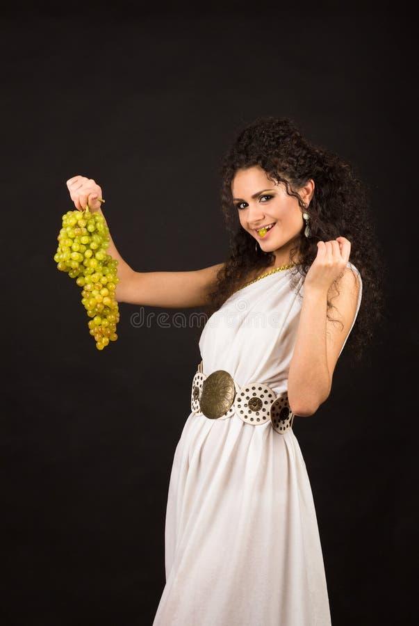 Retrato de una muchacha rizada que sostiene un manojo de uvas imagenes de archivo