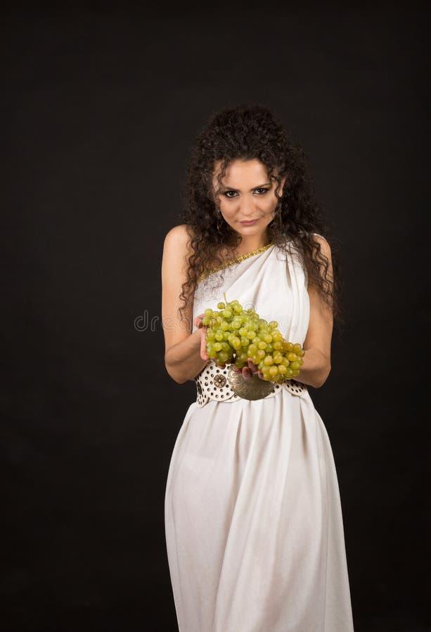Retrato de una muchacha rizada que sostiene un manojo de uvas fotografía de archivo libre de regalías