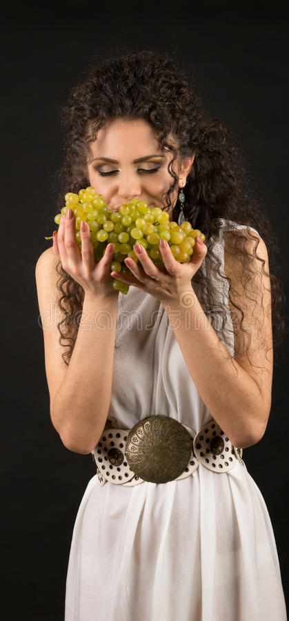Retrato de una muchacha rizada que sostiene un manojo de uvas imagen de archivo libre de regalías
