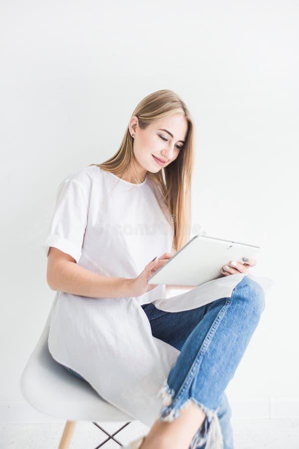 Retrato de una muchacha rubia elegante joven en una camiseta blanca y tejanos usando una tableta en un fondo blanco imagenes de archivo