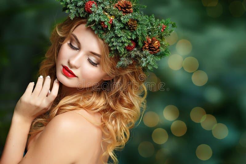 Retrato de una muchacha rubia hermosa con la guirnalda del abeto en su cabeza imagen de archivo libre de regalías