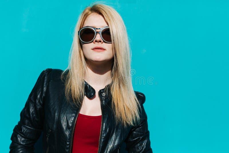 Retrato de una muchacha rubia hermosa joven en gafas de sol enormes en el fondo del día de verano soleado de la pared de la turqu imagenes de archivo