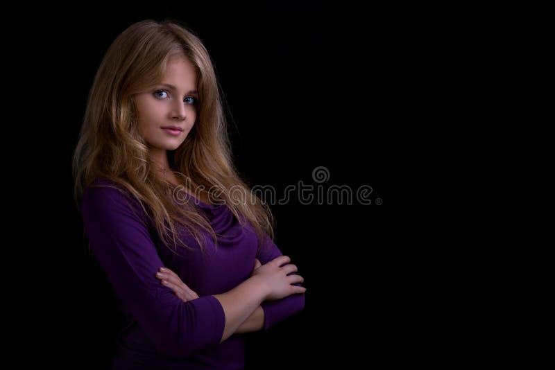 Retrato de una muchacha rubia hermosa que mira a la cámara, t oscuro imágenes de archivo libres de regalías