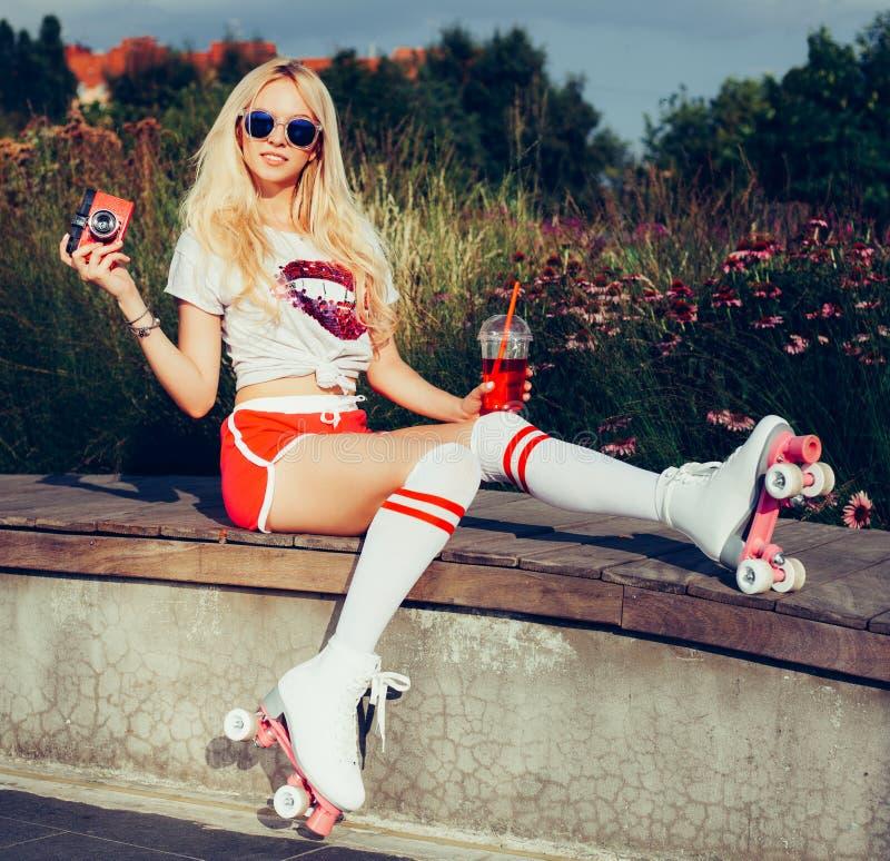 Retrato de una muchacha rubia joven hermosa que presenta con una bebida y de una cámara roja del vintage que se sienta en un banc foto de archivo libre de regalías