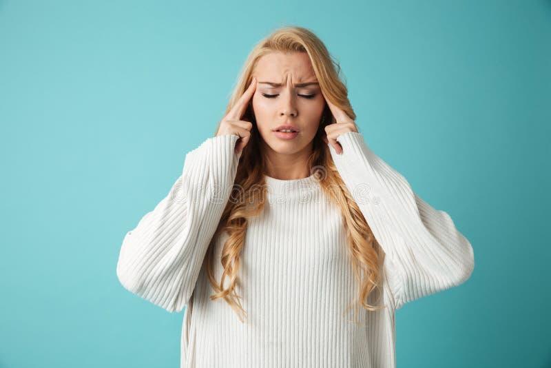 Retrato de una muchacha rubia joven que tiene un dolor de cabeza fotos de archivo libres de regalías