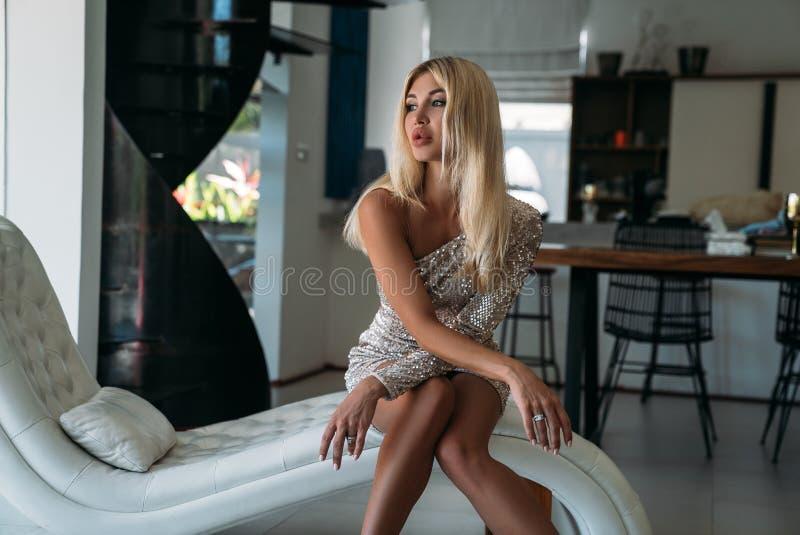 Retrato de una muchacha rubia linda con los labios hermosos grandes que se sientan en el sofá La muchacha en un vestido brillante fotos de archivo libres de regalías