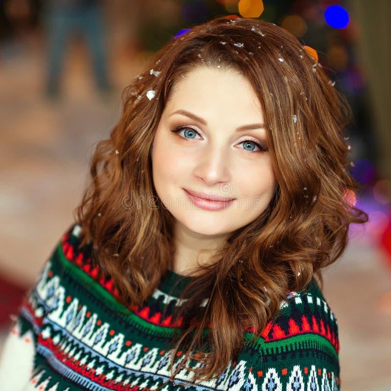 Retrato de una muchacha sonriente en un suéter de punto verde en el backgr imagen de archivo