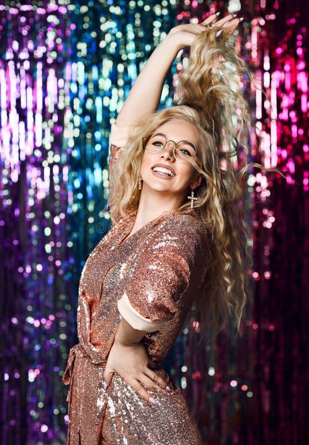 Retrato de una muchacha sonriente feliz en un vestido atractivo elegante con las lentejuelas en un partido de la moda fotos de archivo libres de regalías