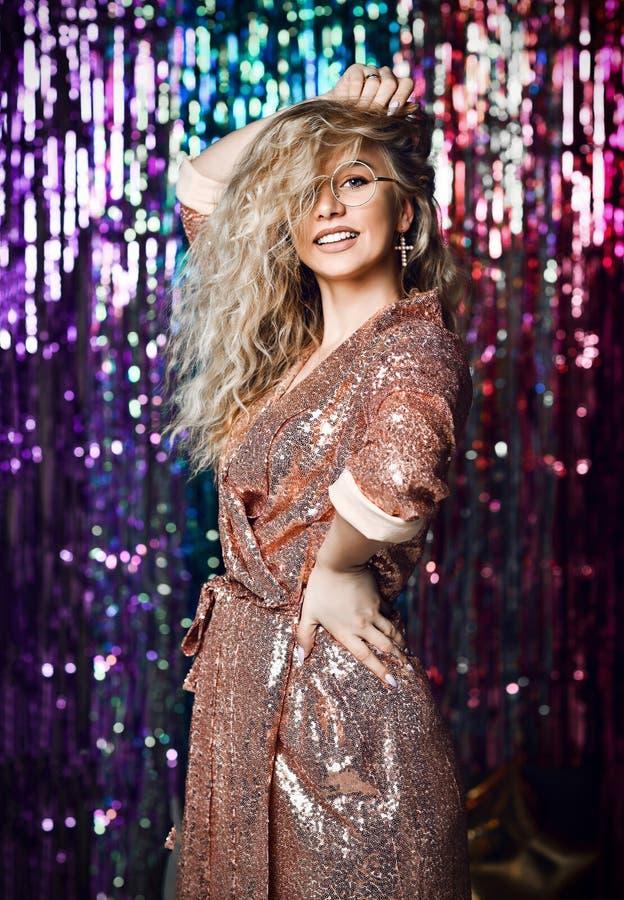 Retrato de una muchacha sonriente feliz en un vestido atractivo elegante con las lentejuelas en un partido de la moda imagen de archivo libre de regalías