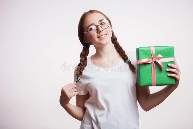 Retrato de una muchacha sonriente feliz que sostiene la actual caja sobre el fondo blanco Una mujer joven en vidrios y una camise foto de archivo