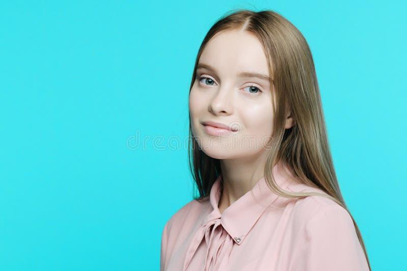 Retrato de una muchacha sonriente joven en fondo azul imagen de archivo libre de regalías