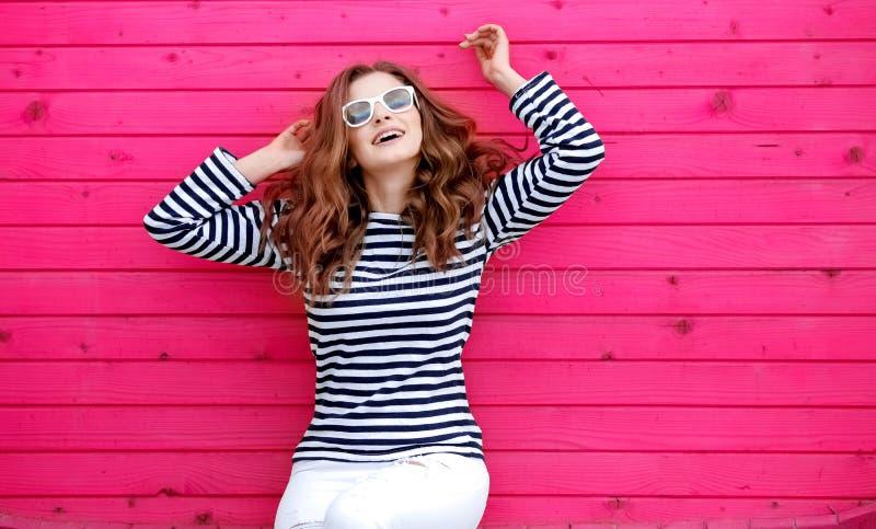Retrato de una muchacha sonriente linda en los vaqueros blancos y de una camiseta rayada cerca de una pared amarilla fotos de archivo
