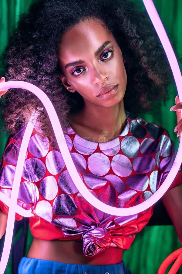 Retrato de una mujer africana con una brillante tapa rosa con luz de neón rosa imagen de archivo