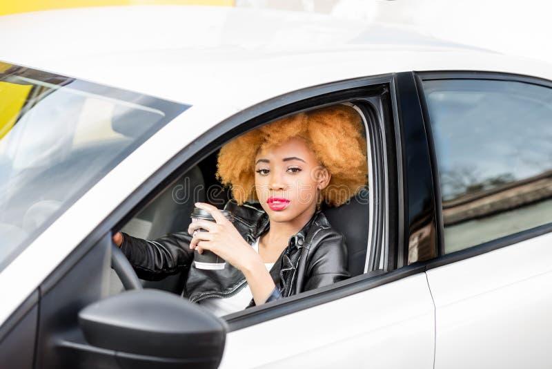 Retrato de una mujer africana hermosa en el coche fotografía de archivo