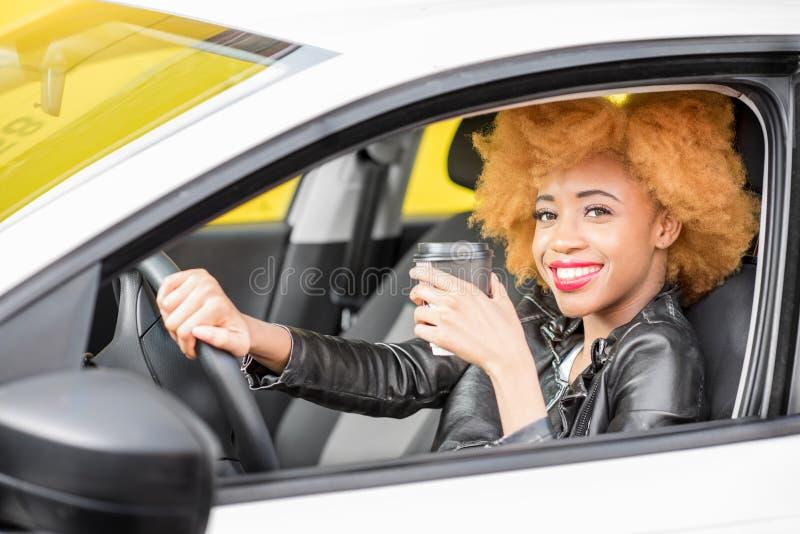 Retrato de una mujer africana hermosa en el coche imagen de archivo