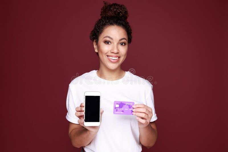 Retrato de una mujer africana joven emocionada que muestra a pantalla en blanco el teléfono móvil aislado sobre rosa foto de archivo