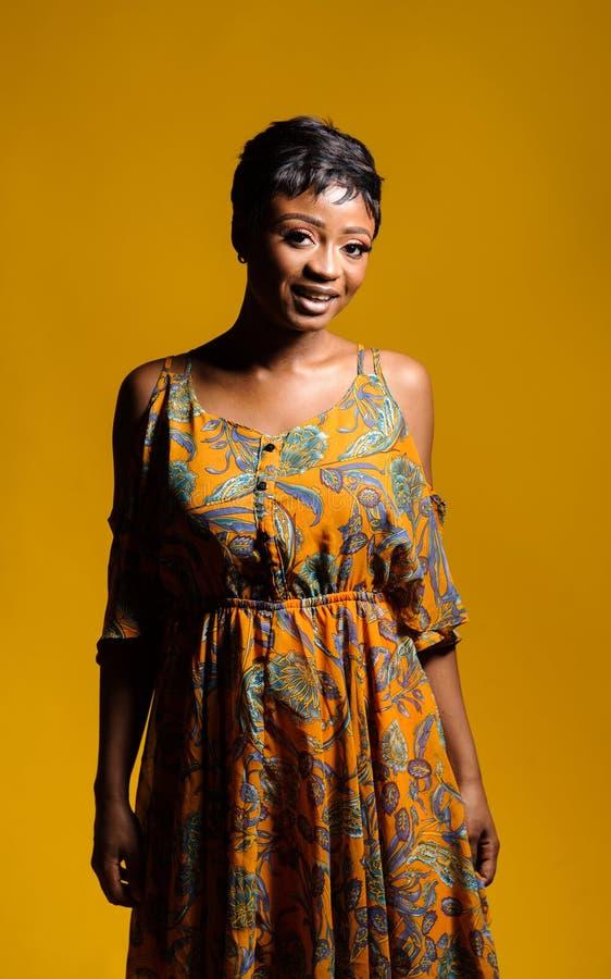 Retrato de una mujer africana joven hermosa sobre fondo amarillo Cuadro del estudio fotos de archivo libres de regalías
