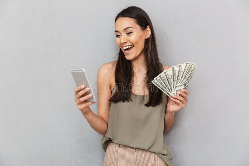 Retrato de una mujer asiática feliz que sostiene billetes de banco del dinero imágenes de archivo libres de regalías