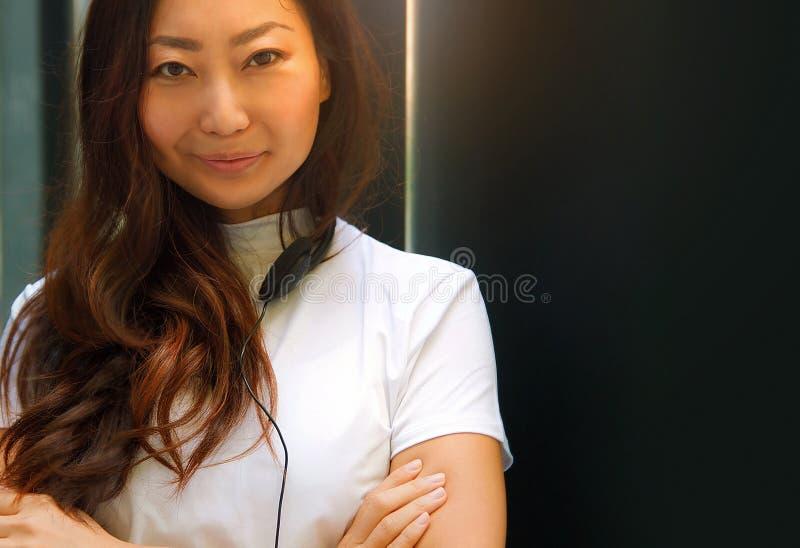 Retrato de una mujer asiática joven en blanco con los auriculares que escucha la música con su smartphone fotos de archivo