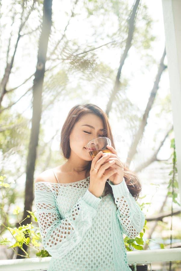 Retrato de una mujer asiática joven que bebe su té de la mañana Cayó r fotos de archivo libres de regalías