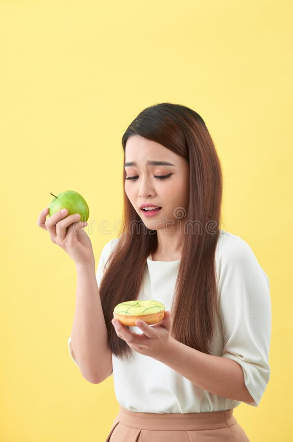 Retrato de una mujer asi?tica joven sonriente que elige entre el bu?uelo y la manzana verde aislados sobre fondo amarillo fotos de archivo libres de regalías