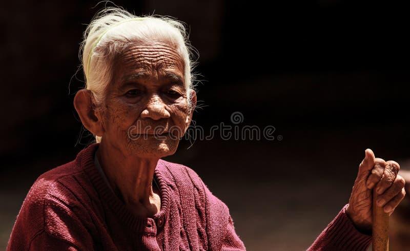Retrato de una mujer asiática mayor que sostiene el bastón que camina en fondo negro fotografía de archivo