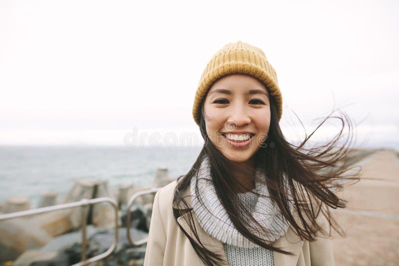 Retrato de una mujer asiática sonriente en ropa del invierno fotos de archivo