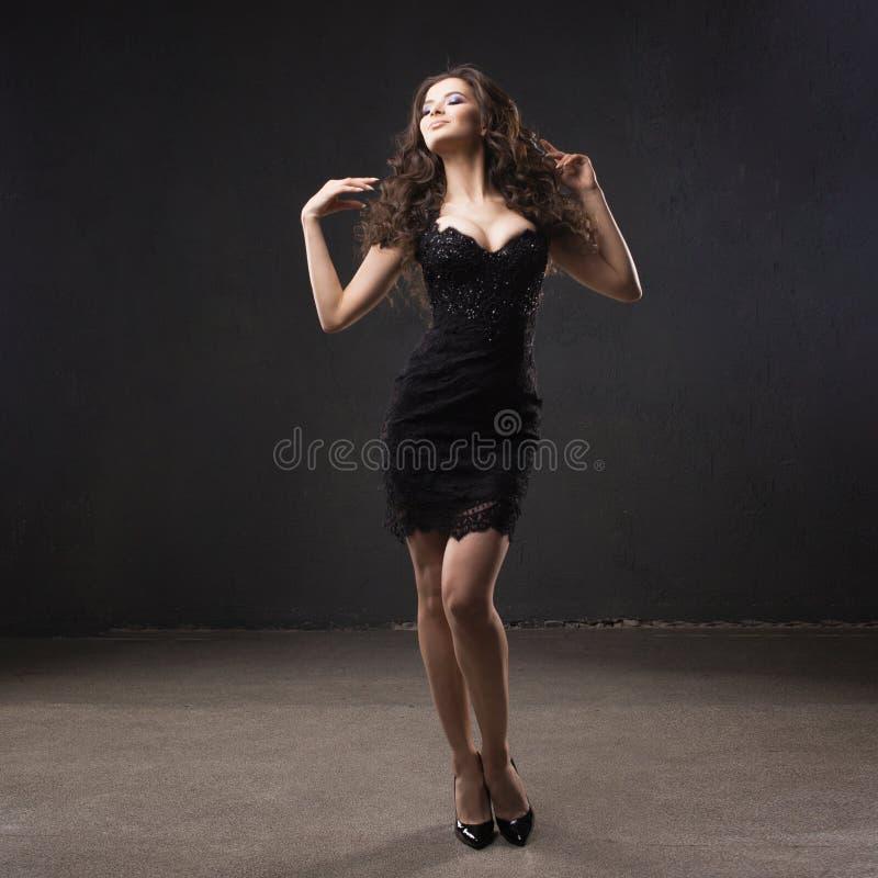 Retrato de una mujer atractiva joven con el pelo rizado magnífico morenita joven en pequeño vestido negro fotografía de archivo