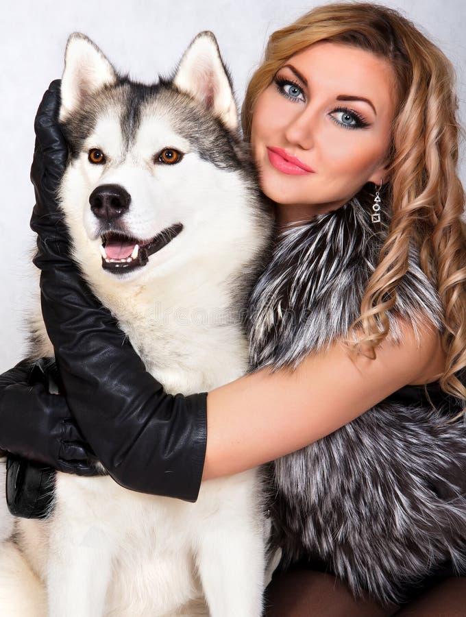 Retrato de una mujer atractiva joven con un perro fornido fotografía de archivo libre de regalías