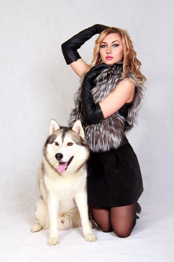 Retrato de una mujer atractiva joven con un perro fornido fotos de archivo