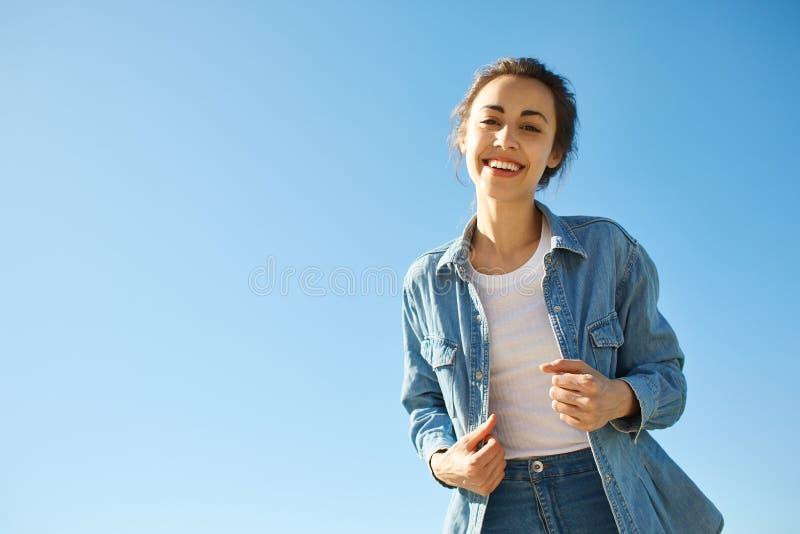 Retrato de una mujer atractiva joven en el fondo del cielo azul fotos de archivo