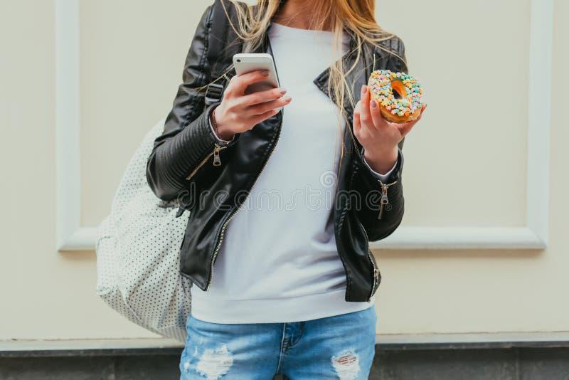 Retrato de una mujer atractiva joven hermosa que come un buñuelo, miradas en su teléfono elegante en la ciudad del europeo de la  imagenes de archivo