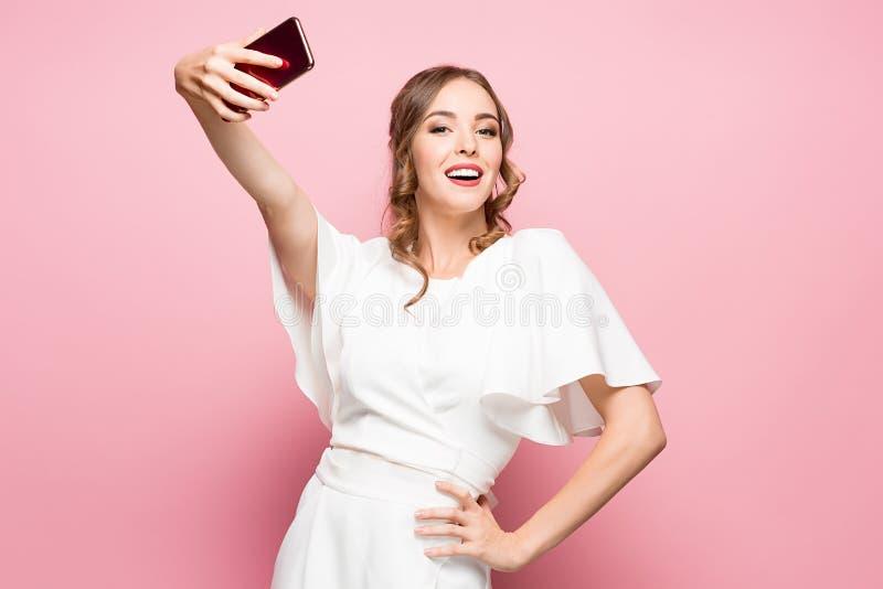 Retrato de una mujer atractiva joven que hace la foto del selfie con smartphone en un fondo rosado fotos de archivo libres de regalías