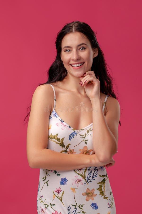 Retrato de una mujer bastante joven en una situaci?n ligera del vestido en fondo rosado en estudio Emociones sinceras de la gente fotos de archivo