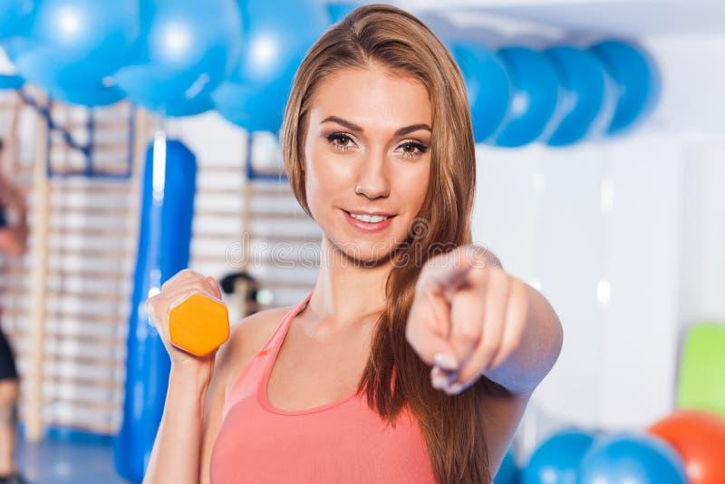 Retrato de una mujer bonita joven que lleva a cabo los pesos (pesa de gimnasia) y que hace indor de la aptitud Pasillo de Crossfi fotos de archivo libres de regalías